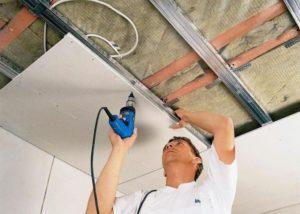 прикручивает гипсокартон к потолку