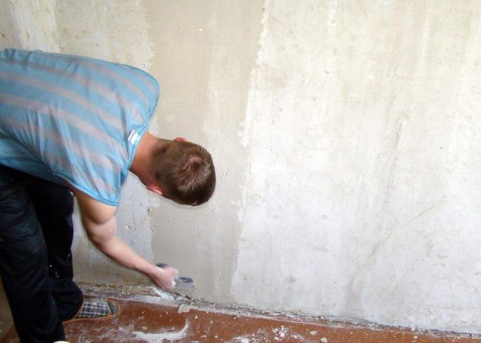 зачищает стену шпателем