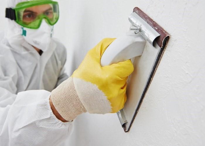 шкурит стену бруском