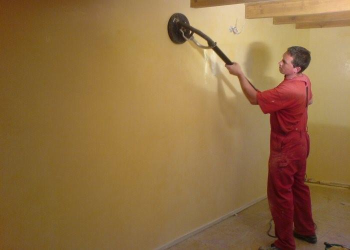 шкурит стены шлифмашинкой
